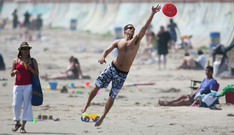 Josh Leuchtag of Houston reaches for a Frisbee on the beach in Galveston in March 2012. Photo: Nick De La Torre / © 2012  Houston Chronicle