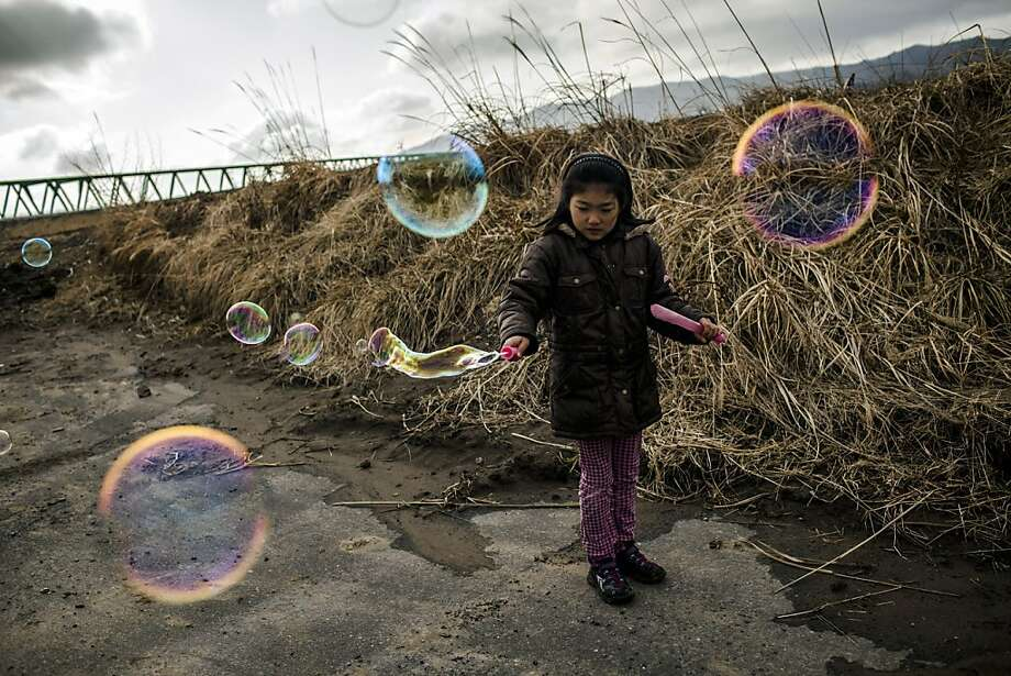 "ISHINOMAKI, JAPAN - MARCH 11: Hikari Oyama, 8,  plays with bubbles, after she and her grandmother payed their respects at the memorial to victims of the last year's tsunami at the Okawa Elementary School, where 74 children were killed and 4 are still missing, on March 11, 2012 near Ishinomaki, Japan.  ""I thought bubble suits better for children rather than incense sticks, so that is why I play with bubble here. and it always makes people laugh and relax"" Oyama's grandmother said. On the one year anniversary, the areas most affected by last year's March 11, 2011 earthquake and subsequent tsunami that left 15,848 dead and 3,305 missing according to Japan's National Police Agency, continue to struggle. Thousands of people still remain without homes living in temporary dwellings. The Japanese government faces an uphill battle with the need to dispose of rubble as it works to rebuild economies and livelihoods. Across the country people are taking part in ceremonies to pay respects to the people who lost their lives. (Photo by Daniel Berehulak /Getty Images) *** BESTPIX *** Photo: Daniel Berehulak, Getty Images"