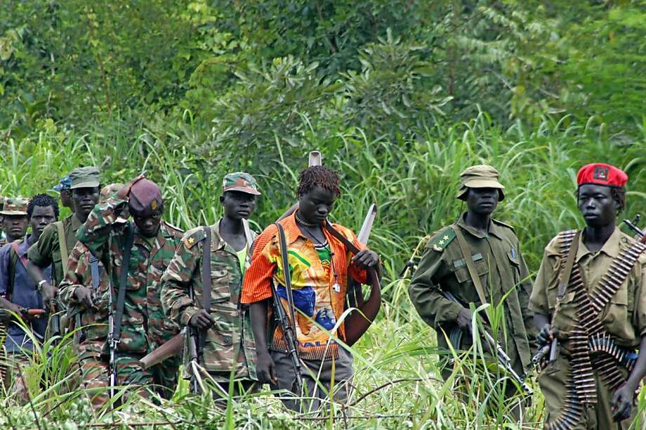 FILE - In this July 31, 2006 file photo, members of Uganda's Lord's Resistance Army are seen as their leader Joseph Kony meets with a delegation of Ugandan officials and lawmakers and representatives from non-governmental organizations, in the Democratic Republic of Congo near the Sudanese border. A video by the advocacy group Invisible Children about the atrocities carried out by jungle militia leader Joseph Kony's Lord's Resistance Army is rocketing into viral video territory and is racking up millions of page views seemingly by the hour. (AP Photo, File) Photo: Anonymous, Associated Press