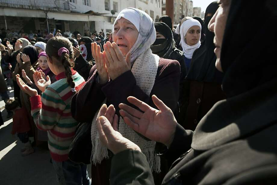A woman weeps as she prays during an anti-government demonstration in Idlib, north Syria, Friday, March 9, 2012. Photo: Rodrigo Abd, Associated Press