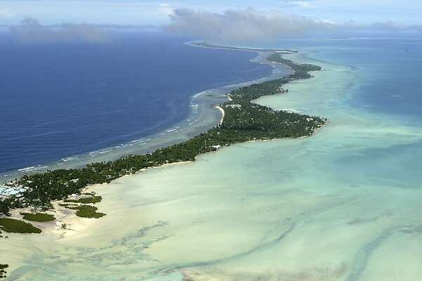 In this March 30, 2004 file photo, Tarawa atoll, Kiribati, is seen in an aerial view. Fearing that climate change could wipe out their entire Pacific archipelago, the leaders of Kiribati are considering an unusual backup plan: moving the populace to Fiji. Kiribati President Anote Tong told The Associated Press on Friday, March 9, 2012 that his Cabinet this week endorsed a plan to buy nearly 6,000 acres on Fiji's main island, Viti Levu. He said the fertile land, being sold by a church group for about $9.6 million, could provide an insurance policy for Kiribati's entire population of 103,000, though he hopes it will never be necessary for everyone to leave.