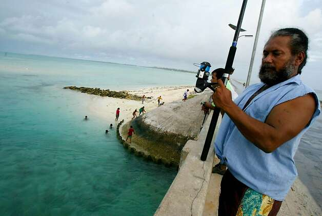 In this March 30, 2004 file photo, a man fishes on a bridge on Tarawa atoll, Kiribati. Fearing that climate change could wipe out their entire Pacific archipelago, the leaders of Kiribati are considering an unusual backup plan: moving the populace to Fiji. Kiribati President Anote Tong told The Associated Press on Friday, March 9, 2012 that his Cabinet this week endorsed a plan to buy nearly 6,000 acres on Fiji's main island, Viti Levu. He said the fertile land, being sold by a church group for about $9.6 million, could provide an insurance policy for Kiribati's entire population of 103,000, though he hopes it will never be necessary for everyone to leave. Photo: Richard Vogel, Associated Press