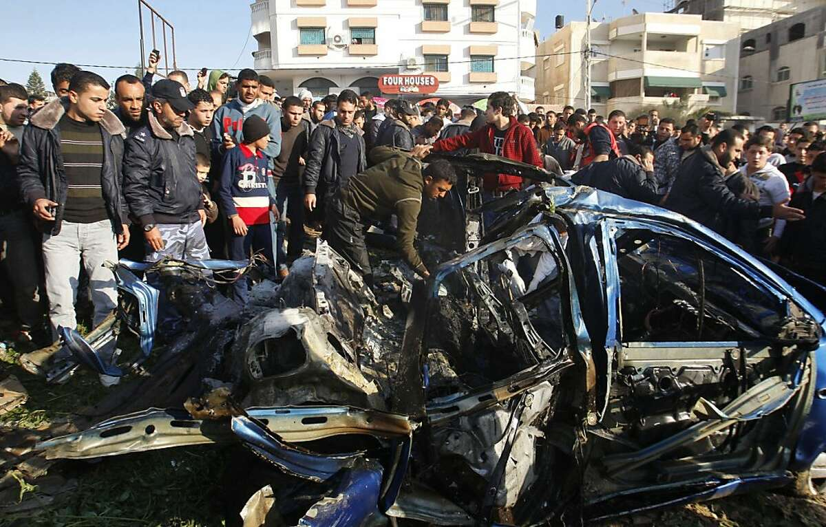 Palestinians gather around the wreckage of a car targeted in an airstrike in Gaza City, Friday, March 9, 2012. An Israeli airstrike killed top Palestinian militant commander Zuhair al-Qaissi and a second militant in Gaza on Friday in the highest profile attack against the coastal strip in months.