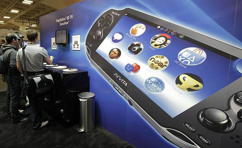 Sony PlayStation PS Vita is shown in foreground as attendees use the Sony PlayStation 3D TV SimuView in the Sony PlayStation booth at the Game Developers Conference in San Francisco, Thursday, March 8, 2012. (AP Photo/Paul Sakuma) Photo: Paul Sakuma, Associated Press