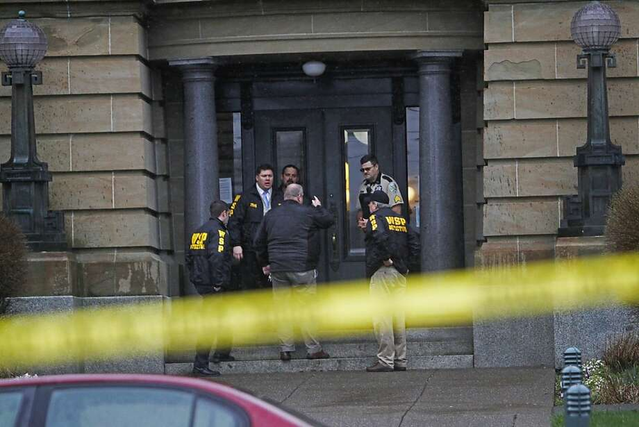 Washington State Patrol detectives investigate outside the Grays Harbor County courthouse where Superior Court Judge Dave Edwards was stabbed and corrections officer Polly Davin was shot during a confrontation in the courthouse in Montesano, Wash. on Friday, March 9, 2012. (AP Photo/The Seattle Times, Mark Harrison) Photo: Mark Harrison, Associated Press