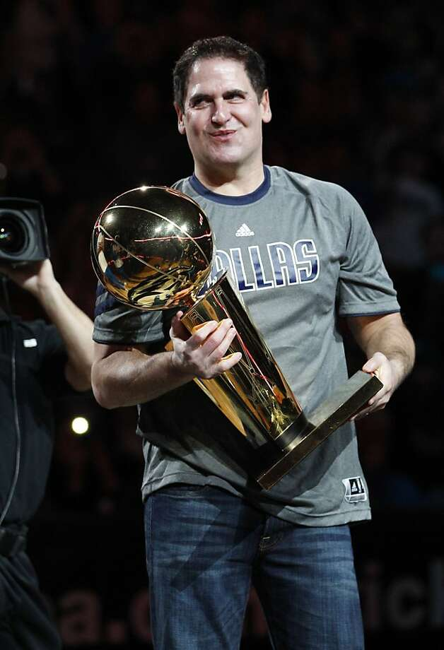 Dallas Mavericks owner Mark Cuban holds the championship trophy for last season before the Mavericks' NBA basketball game against the Miami Heat in Dallas, Sunday, Dec. 25, 2011. (AP Photo/LM Otero) Photo: LM Otero, Associated Press