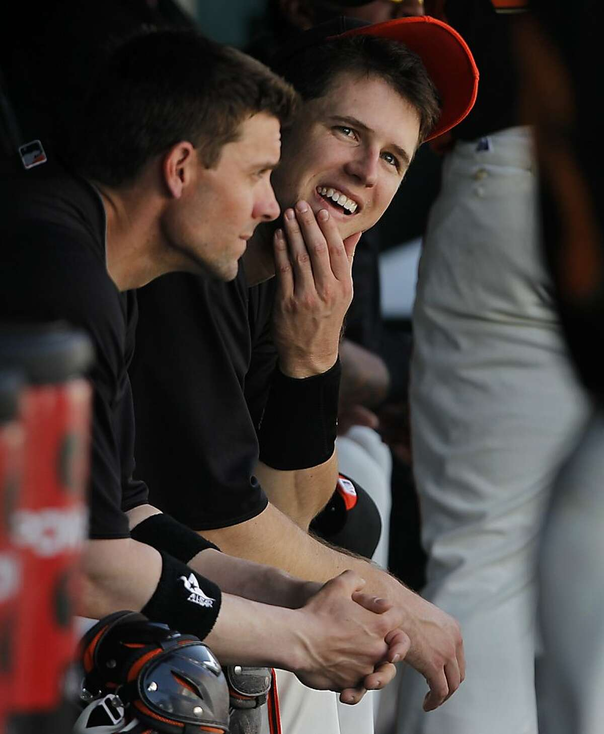 Buster Posey sits with backup catcher Chris Stewart in the dugout during the San Francisco Giants Cactus League spring training game against the Cincinnati Reds in Scottsdale, Ariz. on Friday, March 9, 2012. It was Posey's first game since his season-ending ankle injury last May.