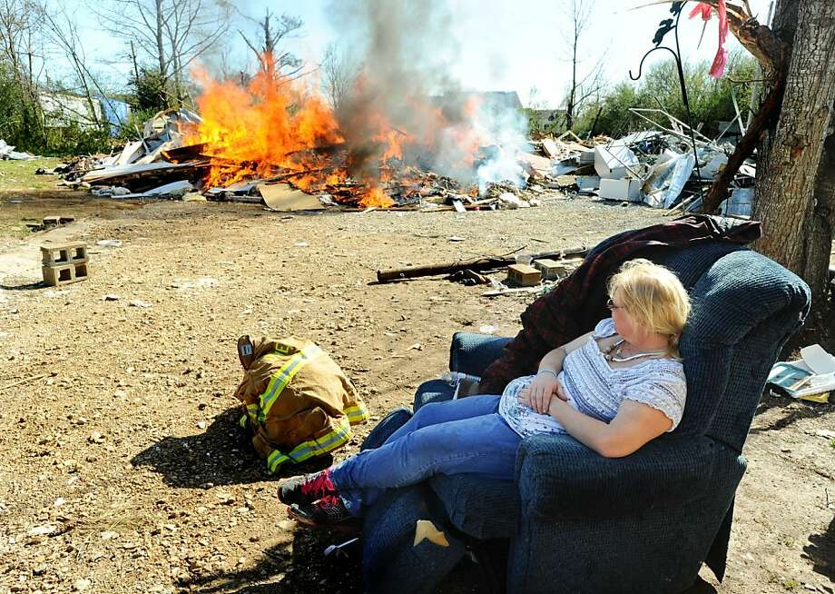 Patty Goar sits in a recliner and watches debris from her former home burn on Nick Davis Road in Limestone County, Ala., on Saturday, March 10, 2012. There are no plans to remove debris from the March 3 tornado, leaving residents to fend for themselves. (AP Photo/The Decatur Daily, Gary Cosby Jr.) Photo: Gary Cosby Jr., Associated Press