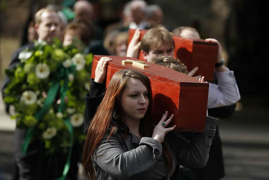 Pallbearers carry a casket during a funeral at West Laurel Hill Cemetery, Friday, March 9, 2012, in Bala Cynwyd, Pa., for five 19th-century Irish immigrants whose remains were excavated from the Duffy's Cut site. Researchers believe the site in Malvern, Pa., contains the remains of about 50 Irish immigrants who died weeks after coming to Pennsylvania to build a railroad in 1832. (AP Photo/Matt Rourke) Photo: Matt Rourke, Associated Press