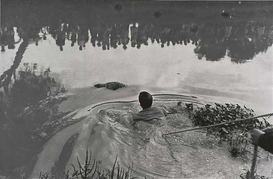 """Rescate de un ahogado en Xochimilco con p blico reflejado en el aqua, (Retrieval of a drowned body from Lake Xochimilco with the public reflected in the water) (1960) gelatin silver print by Enrique Metinides  13 3/4 x 20 3/4 in.   San Francisco Museum of Modern Art Photo: Enrique Metinides"