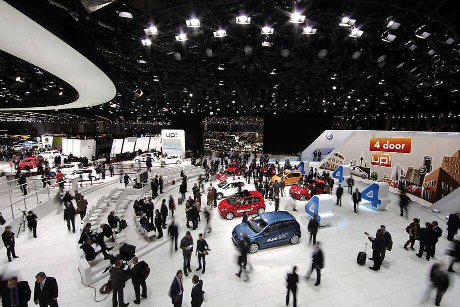 Visitors look at a row of VW Up automobiles on the Volkswagen AG stand during the first press day of the Geneva International Motor Show in Geneva, Switzerland, on Tuesday, March 6, 2012. The 82nd Geneva International Motor Show will showcase the latest models from the auto industry's leading manufacturers at the Palexpo exhibition centre this week. Photo: Jason Alden, Bloomberg