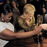 "Octavia Spencer with the Oscar for best actress in a supporting role for ""the Help"", left, and Meryl Streep with the Oscar for best actress in a leading role for ""The Iron Lady"" examine their trophies at the Governors Ball following the 84th Academy Awards on Sunday, Feb. 26, 2012, in the Hollywood section of Los Angeles. (AP Photo/Chris Pizzello)"