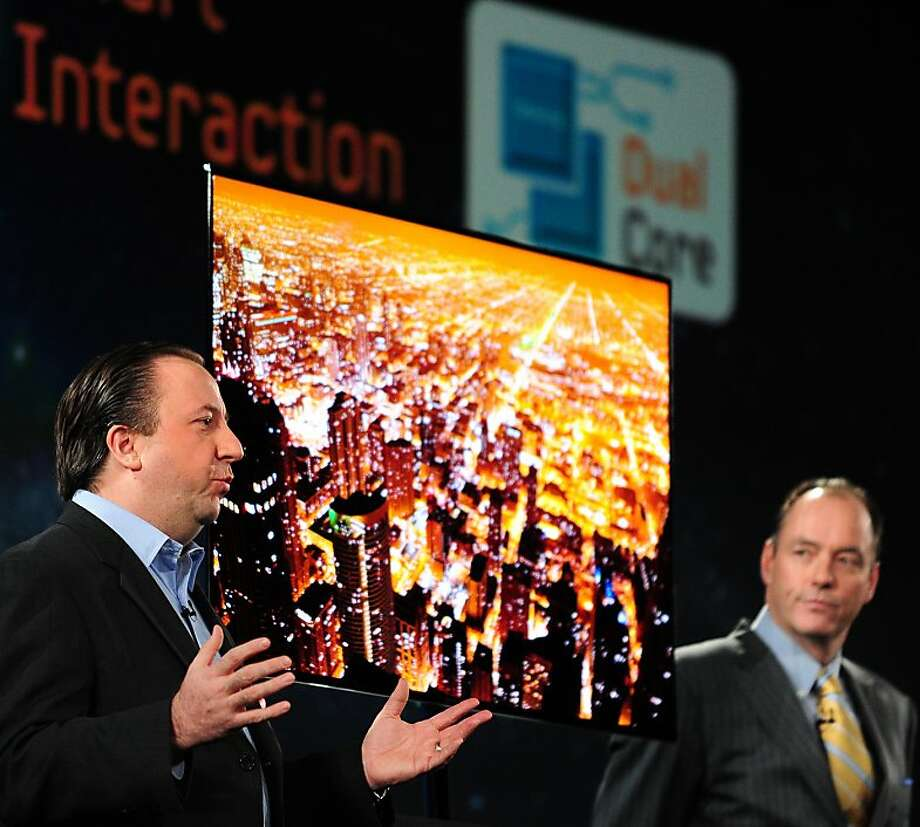Tim Baxter (R), President of Samsung Electronics America looks on as Joe Stinziano (L), senior VP of Samsung Electronics America speaks at the unveiling of Samsung's 55-inch Super OLED HDTV (C) during Press Day Events at the annual Consumer Electronics Show on January 9, 2012 in Las Vegas, Nevada.  AFP PHOTO / Frederic J. BROWN (Photo credit should read FREDERIC J. BROWN/AFP/Getty Images) Photo: Frederic J. Brown, AFP/Getty Images