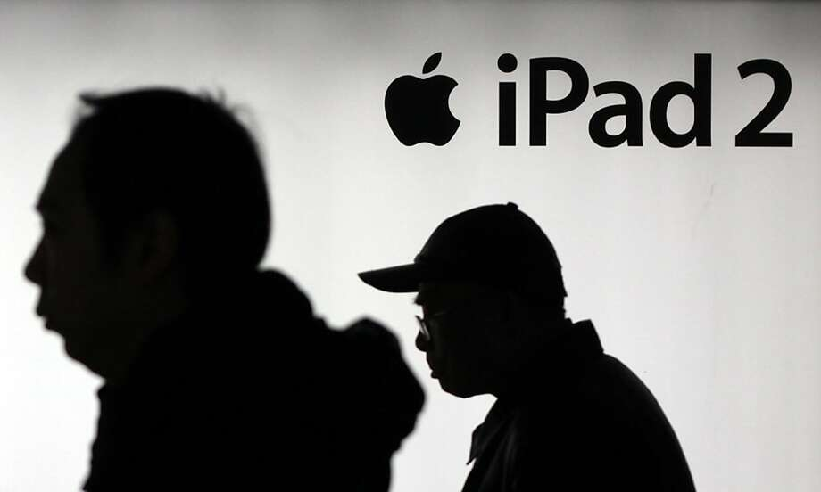 FILE-In this Feb. 28, 2012 file photo, men walk past an advertisement of Apple's iPad 2 in Shanghai, China. In its latest statement on a simmering dispute over the iPad brand name, Apple Inc. said Tuesday, March 13, 2012, that Proview Electronics' insistence that it still owns the mainland China iPad trademarks is misleading and unfair. (AP Photo/Eugene Hoshiko, File) Photo: Eugene Hoshiko, Associated Press