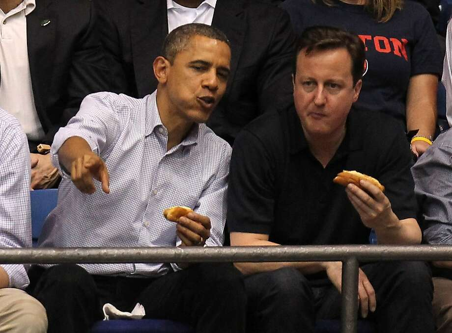 DAYTON, OH - MARCH 13:  U.S. President Barack Obama (L) and British Prime Minister David Cameron (R) eat a hot dog as they watch the first half at UD Arena as the Western Kentucky Hilltoppers take on the Mississippi Valley State Delta Devils in the first round of the 2011 NCAA men's basketball tournament on March 13, 2012 in Dayton, Ohio.  (Photo by Gregory Shamus/Getty Images) Photo: Gregory Shamus, Getty Images