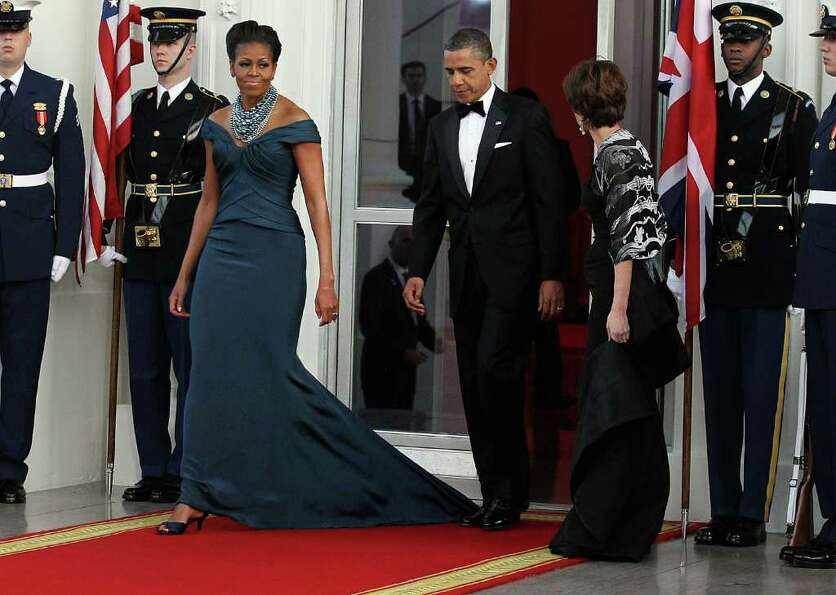 U.S. President Barack Obama (C) accidentially steps on First lady Michelle Obama's dress as they wal