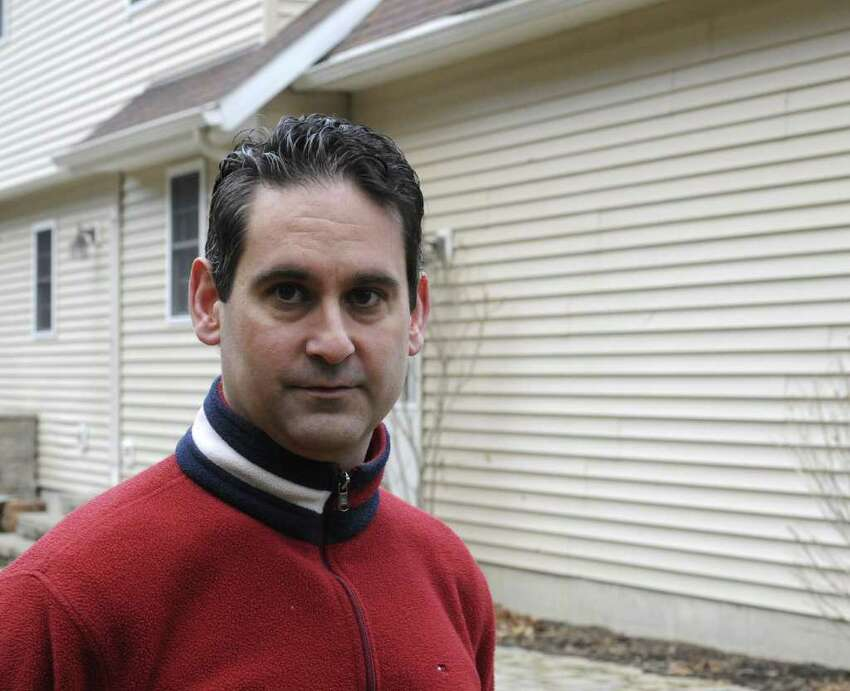 Eugene Dallas stands in front of the siding on his home in Wilton, N.Y., March 8, 2012. ( Skip Dickstein / Times Union)