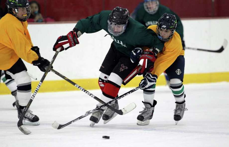 Eastern Middle School forward Nico LeBlanc weaves his way through two Western Middle School defenders during the championship match between the middle schools of Greenwich at Hamill Rink Wednesday night. Eastern led the entire way to capture the gold championship. medal.  © J. Gregory Raymond Photo: J. Gregory Raymond / © J. Gregory Raymond for The Greenwich Time