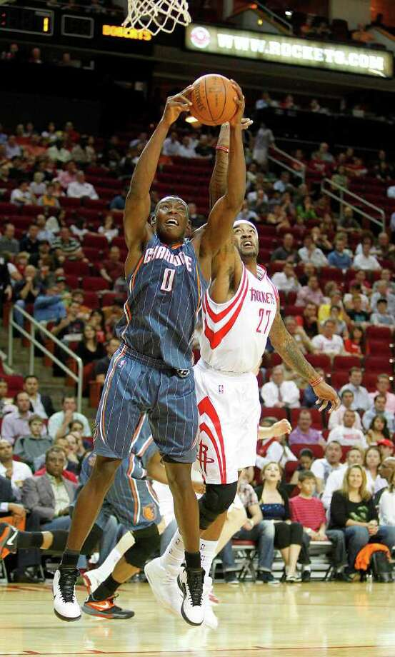 Charlotte Bobcats center Bismack Biyombo (0) stops Houston Rockets center Jordan Hill (27) from scoring in the first period during the basketball game at Toyota Center on Wednesday, March 14, 2012, in Houston. Photo: Mayra Beltran, Houston Chronicle / © 2012 Houston Chronicle