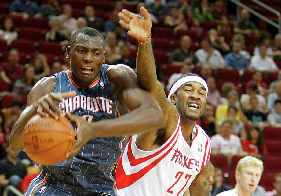 Charlotte Bobcats center Bismack Biyombo (0) takes possession of the ball as Houston Rockets center Jordan Hill (27) tries to steal in the first period during the basketball game at Toyota Center on Wednesday, March 14, 2012, in Houston. Photo: Mayra Beltran, Houston Chronicle / © 2012 Houston Chronicle
