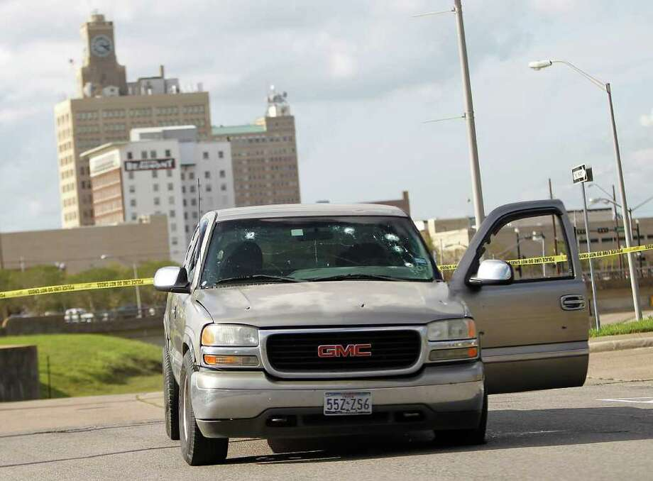 A truck riddled with bullet holes sits a few blocks from the Jefferson County Courthouse where a gunman shot four people outside of the courthouse, killing one. Photo: Karen Warren, Houston Chronicle / © 2012  Houston Chronicle