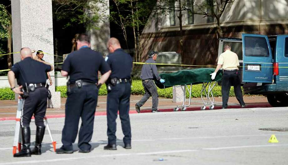 Medical examiners take a woman's body away from the steps of the Jefferson County Courhouse hours after a gunman shot four people outside of the courthouse, killing one woman about 11:30am,  Wednesday, March 14, 2012, in Beaumont. Photo: Karen Warren, Houston Chronicle / © 2012  Houston Chronicle