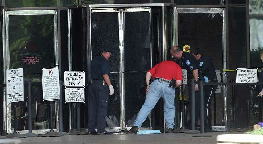 Beaumont police officers investigate the front door of the Jefferson County Courhouse hours after a gunman shot four people outside of the courthouse, killing one woman about 11:30am. Photo: Karen Warren, Houston Chronicle / © 2012  Houston Chronicle