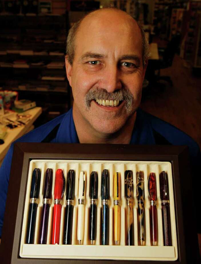 Larry Dromgoole shows off Visconti pens. Dromgoole's is a laid-back Rice Village store where on any given Saturday, regulars enjoy hot wings and pizza. Photo: James Nielsen / © 2011 Houston Chronicle