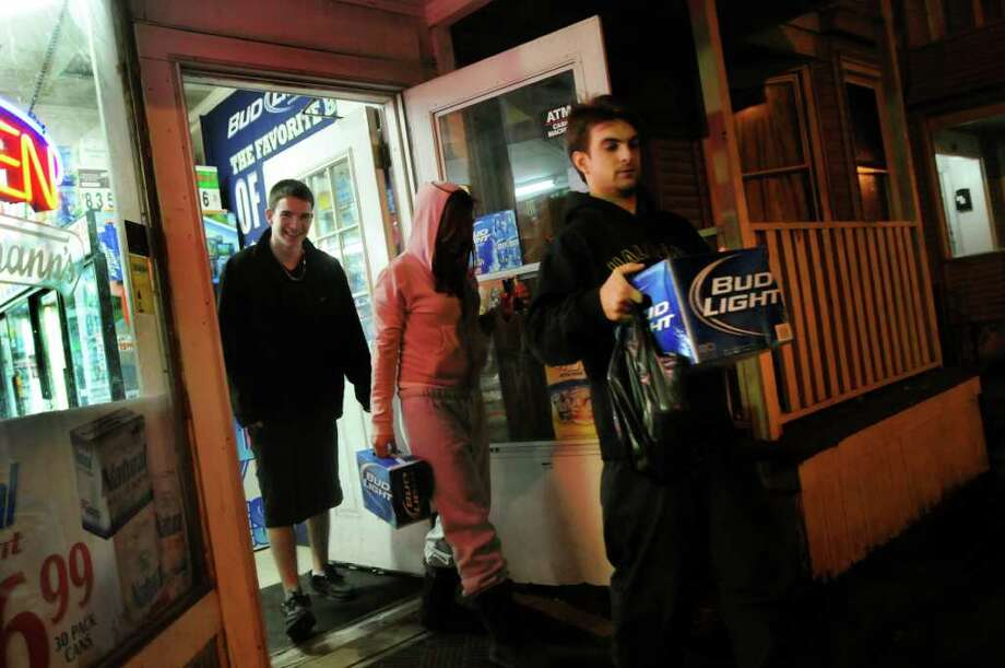 Young adults carry their beer purchases from a corner store in the student ghetto on Thursday, March 8, 2012, in Albany, N.Y. (Cindy Schultz / Times Union) Photo: Cindy Schultz / 00016720A