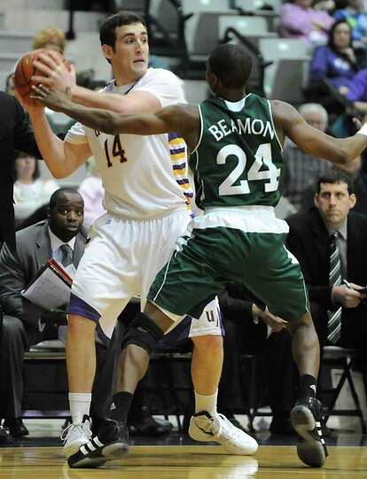 UAlbany's Sam Rowley is guarded by Manhattan's George Beamon during a basketball game March 14, 2012
