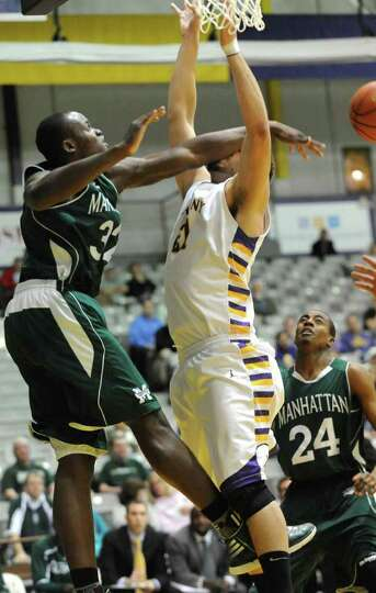 UAlbany's Blake Metcalf gets a forearm in the face from Manhattan's Rhamel Brown during a basketball