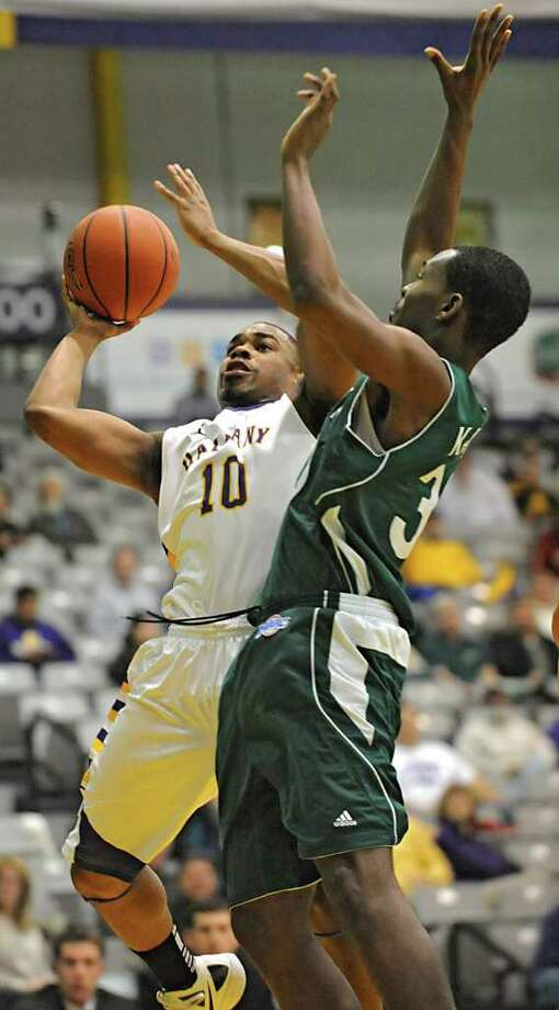 UAlbany's Mike Black drives to the basket against Manhattan's Donovan Kates during a basketball game March 14, 2012 in Albany, N.Y. (Lori Van Buren / Times Union) Photo: Lori Van Buren