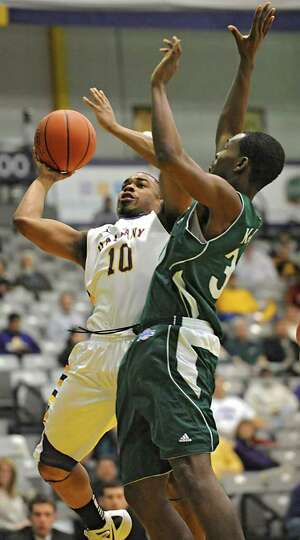 UAlbany's Mike Black drives to the basket against Manhattan's Donovan Kates during a basketball game