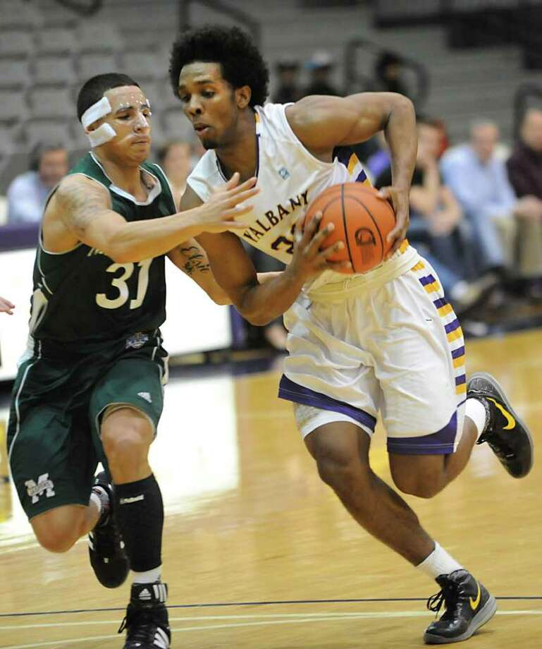 UAlbany's Gerardo Suero drives around Manhattan's Michael Alvarado during a basketball game March 14, 2012 in Albany, N.Y. (Lori Van Buren / Times Union) Photo: Lori Van Buren