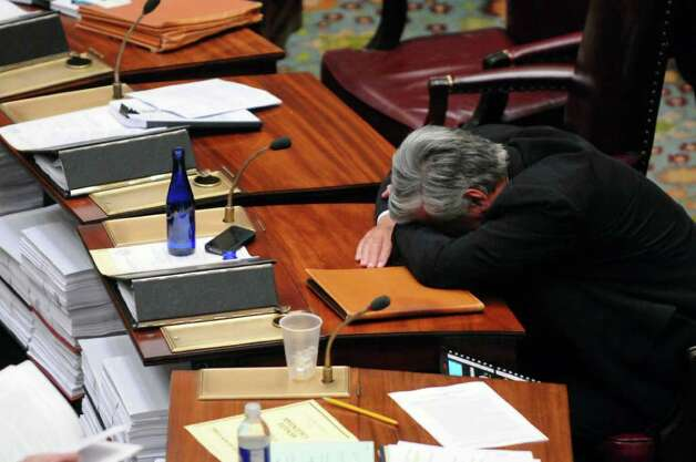 Senate Majority Leader Dean G. Skelos puts his head on his desk  as he laughs at something told to him by fellow Senator Joseph Robach, as they and fellow Republicans were waiting in the Senate chamber at about 9 p.m. on Wednesday night March 14, 2012 in Albany, N.Y. (Philip Kamrass / Times Union ) Photo: Philip Kamrass