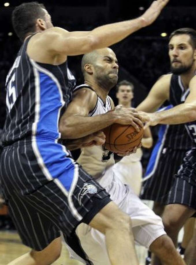 Tony Parker powers through Hedo Turkoglu and Ryan Anderson as the Spurs beat the Orlando Magic 122-111 at the AT&T Center  on March 14, 2012  Tom Reel/ San Antonio Express-News (TOM REEL / San Antonio Express-News)