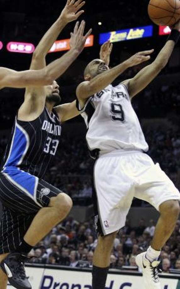Tony Parker leaves Ryan Anderson behind to score as the Spurs play the Orlando Magic at the AT&T Center  on March 14, 2012  Tom Reel/ San Antonio Express-News (TOM REEL / San Antonio Express-News)