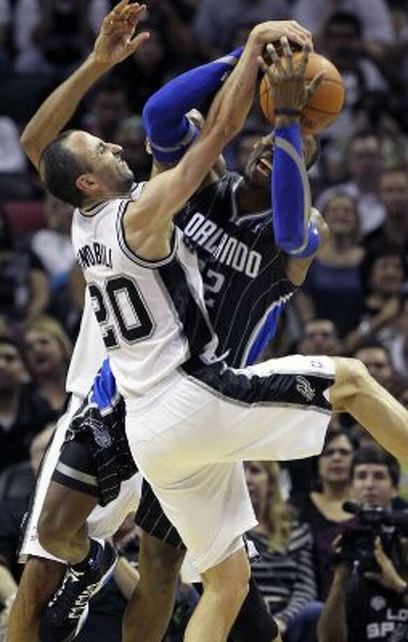 Manu Ginobili rushes in to take a stab at the ball as Dwight Howard posts against Tim Duncan in the fourth quarter as the Spurs play the Orlando Magic at the AT&T Center  on March 14, 2012  Tom Reel/ San Antonio Express-News (TOM REEL / San Antonio Express-News)