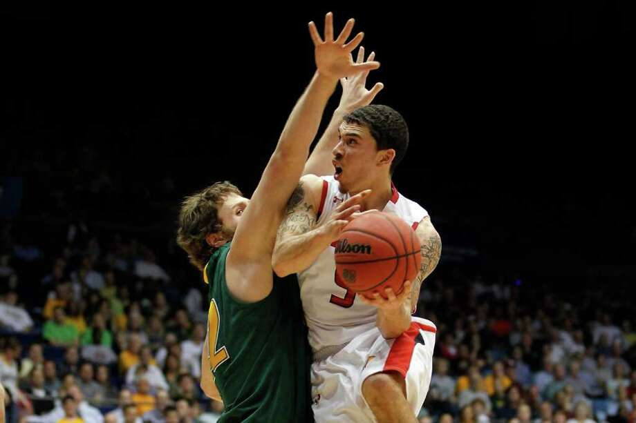 Lamar's Mike James, right, finds a two-arm roadblock denying his access to the basket. Ben Crenca and his Vermont teammates made offense hard to come by for the Cardinals on Wednesday. Photo: Gregory Shamus / 2012 Getty Images
