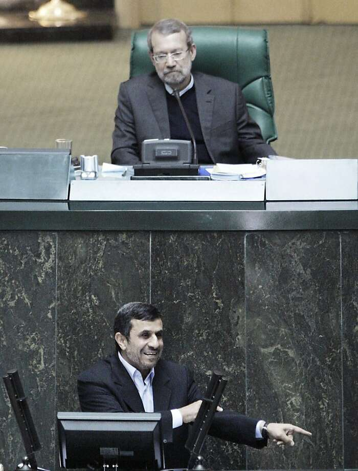 Parliament speaker Ali Larijani, top, listens to Iranian President Mahmoud Ahmadinejad, bottom, as he answers questions in an open session in parliament in Tehran, Iran, Wednesday, March 14, 2012. Iran's parliament began on Wednesday to question President Mahmoud Ahmadinejad over a long list of accusations, including that he mismanaged the nation's economy and challenged the country's supreme leader. Ahmadinejad is the first president in the country's history to be hauled before the Iranian parliament, a serious blow to his standing in a conflict pitting him against lawmakers. Photo: Vahid Salemi, Associated Press
