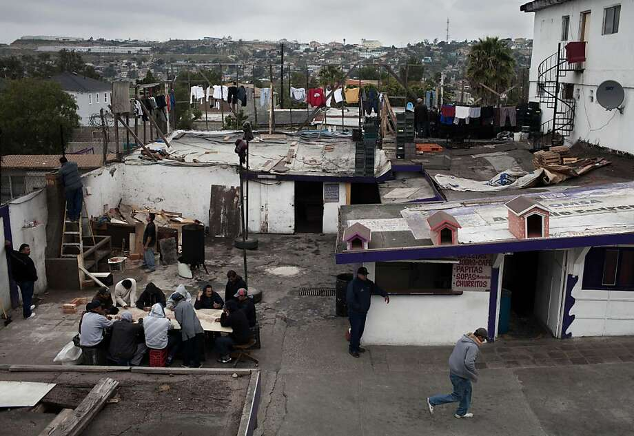 """In this March 6, 2012 photo, people sit at a table as they separate beans for a meal at the CIRAD drug rehabilitation center in Tijuana, Mexico.  In a relatively new phenomenon, young people are increasingly being used as """"mules,"""" or distributors for drug traffickers, whether to cross drugs into the U.S. or to sell, especially along the border, according to Victor Clark, a social anthropologist and specialist on drug trafficking in this region. The drug rehab center houses about 500 addicts, and about 100 of them are minors. Photo: Alejandro Cossio, Associated Press"""