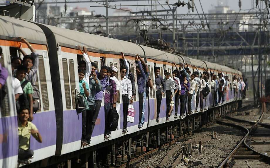 Indian commuters ride in the doorway on a local train in Mumbai, India, Wednesday, March 14, 2012. The Indian Railway Minister unveiled the annual budget Wednesday for the railway network which is one of the world's largest, with some 14 million passengers daily. (AP Photo/Rafiq Maqbool) Photo: Rafiq Maqbool, Associated Press
