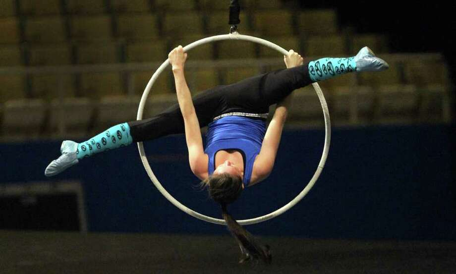 "Performer Lisa Skinner practices the aerial hoops in Cirque du Soleil's production of ""Quidam,"" Wednesday, March 14, 2012. The show runs through Sunday at the Freeman Coliseum. The storyline follows a bored young girl who imagines a whimsical world as a means of escape from her monotonous existence. Photo: San Antonio Express-News"