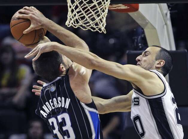 Manu Ginobili challenges Ryan Anderson under the basket in the first half as the Spurs play the Orlando Magic at the AT&T Center  on March 14, 2012  Tom Reel/ San Antonio Express-News (TOM REEL / San Antonio Express-News)