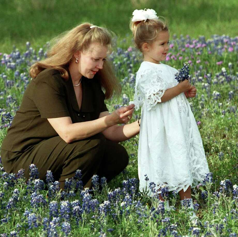 Beth Ricks adjusts daughter Katie's dress while taking pictures in a field of bluebonnets on April 3, 1998. Photo: DOUG SEHRES, Express-News File Photo
