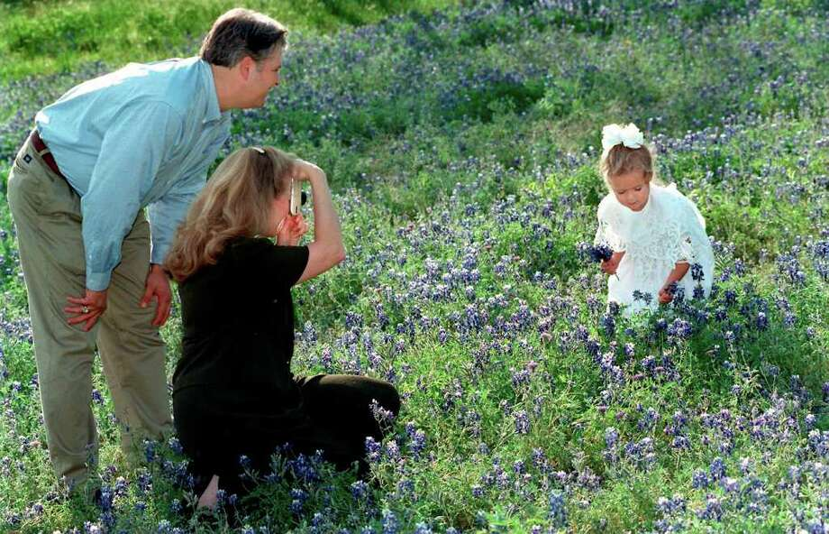 Beth Ricks takes photos of daughter Katie, 4 amongst the bluebonnets while her husband Phil helps pose and direct Katie on April 3, 1998. Photo: DOUG SEHRES, Express-News File Photo