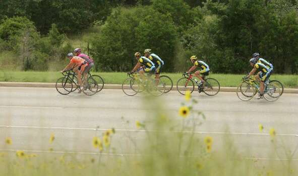 Members of two bicycle racing clubs, Solar Eclipse and Geri-Atrix, pass wildflowers as they near the end of a 60-mile training ride on Loop 1604 in Northwest Bexar County on June 24, 2007. Photo: Robert McLeroy, Express-News File Photo / San Antonio Express-News