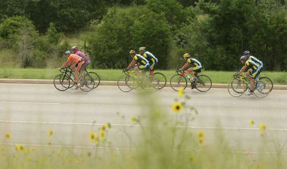 Members of two bicycle racing clubs, Solar Eclipse and Geri-Atrix, pass wildflowers as they near the
