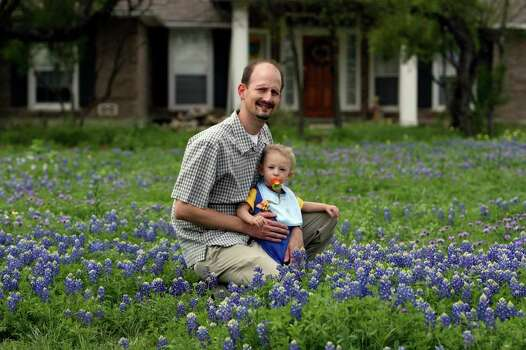 "Paul Jurena sits in his front yard with his son Christopher, 16 months, on March 28, 2007. Jurena likes to grow wildflowers in his yard and says letting the plants ""go to seed"" is key when it comes to having success with wildflowers. Photo: JOHN DAVENPORT, Express-News File Photo / SAN ANTONIO EXPRESS-NEWS"