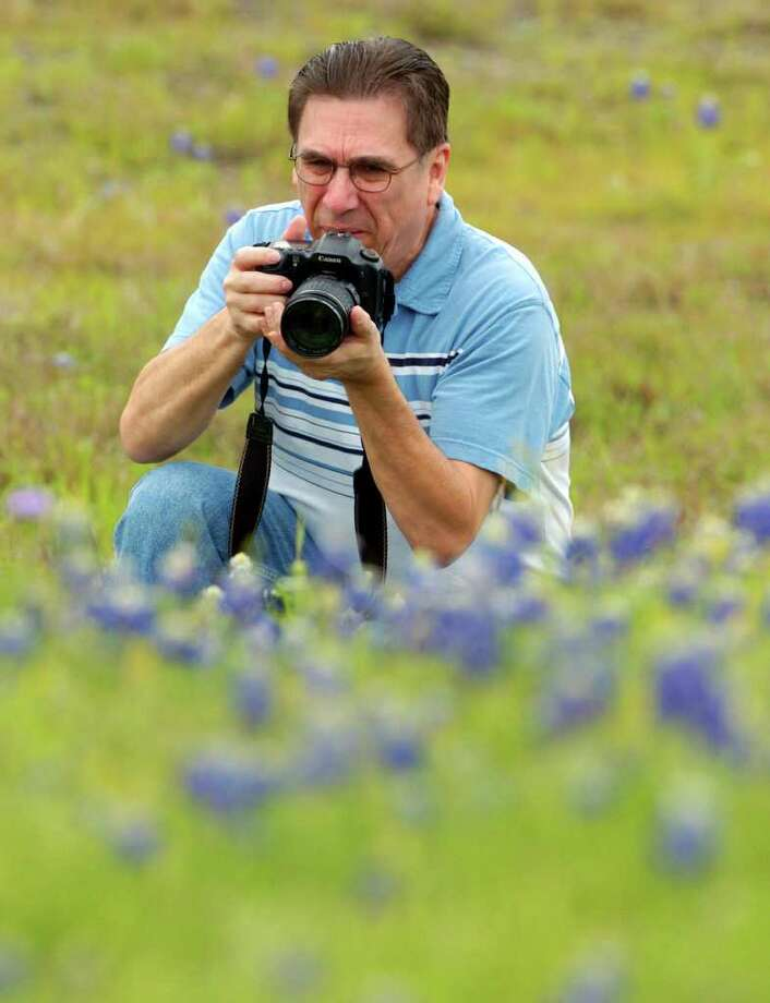 Rich Olivieri takes pictures of bluebonnets on March 29, 2005 near Loop 1604 and U.S. 281 North. Photo: JOHN DAVENPORT, Express-News File Photo / SAN ANTONIO EXPRESS-NEWS